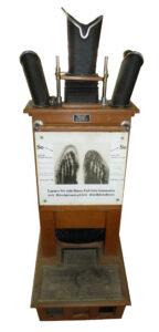 """Der landläufig sogenannte """"Schuh-Röntgenapparat"""" gehörte in den 1920-er Jahren zum Bild exklusiver Schuhgeschäfte.1920 war er auf einer Fachmesse in Boston erstmals der Öffentlichkeit vorgestellt worden. Sogar bis in die 1960-er Jahre waren diese Geräte im Einsatz zu finden.Es diente der Feststellung der Passgenauigkeit besonders bei Kinderschuhen. Das Pedoskop war ausgestattet mit einer SIEMENS Röntgen-Röhre und verfügte über 3 Blickschächte für den Schuhfachverkäufer.<br /> Aufgrund der erst in den 1960er Jahren gewonnenen Erkenntniss über die gesundheitlichen Gefahren durch Röntgenstrahlung wurden der Einsatz dieser Geräte 1961 sofort gesetzlich verboten. Umgehend verschwanden die Geräte aus den Schuhgeschäften."""